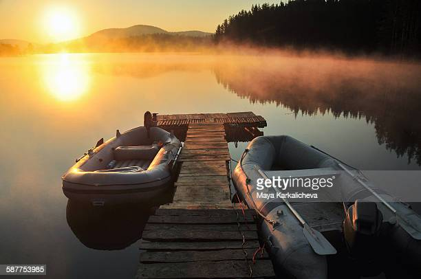 Inflatable raft by wooden pier at sunrise lake
