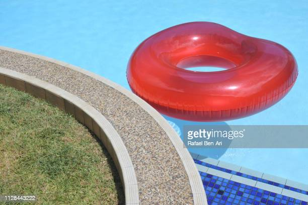 inflatable ring floating in a swimming pool - rafael ben ari fotografías e imágenes de stock
