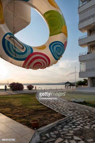 inflatable ring near seaside on a sunny day in cesme. - emreturanphoto stock pictures, royalty-free photos & images