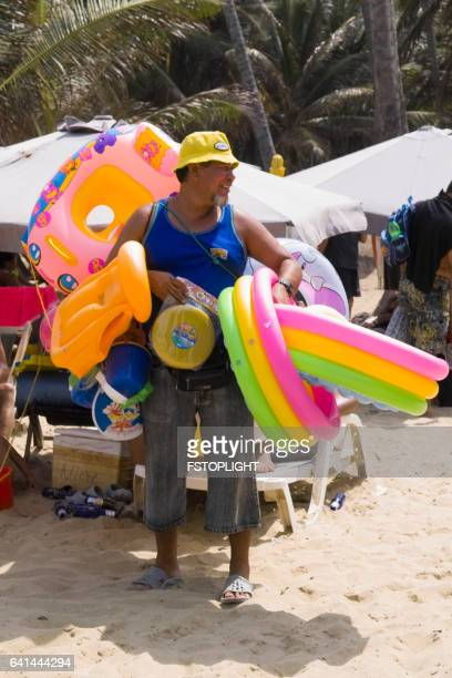 inflatable seller at the beach travel like a local - brief - fstoplight stock photos and pictures