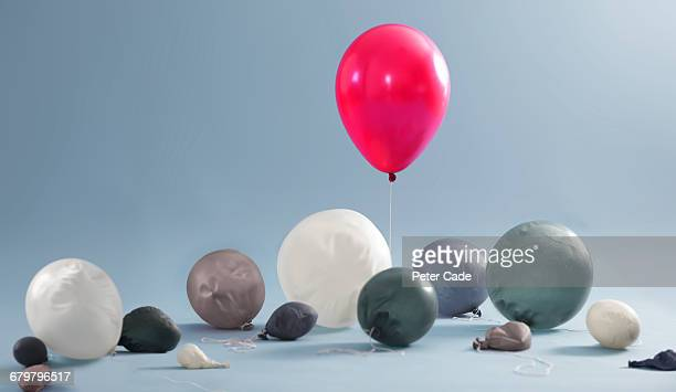 Inflated balloon surrounded by deflated balloons