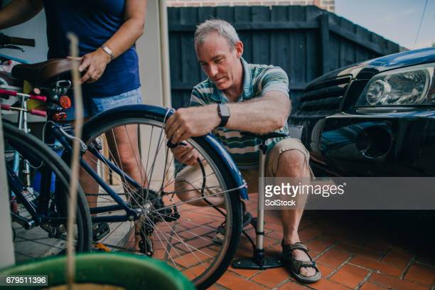 inflating the tire on a bicycle - air pump stock photos and pictures
