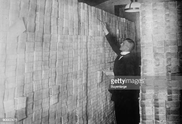 Inflation in Weimar Germany has paper money stacked from Floor to Ceiling in a Berlin Bank banker is counting sheaves of bundled notes