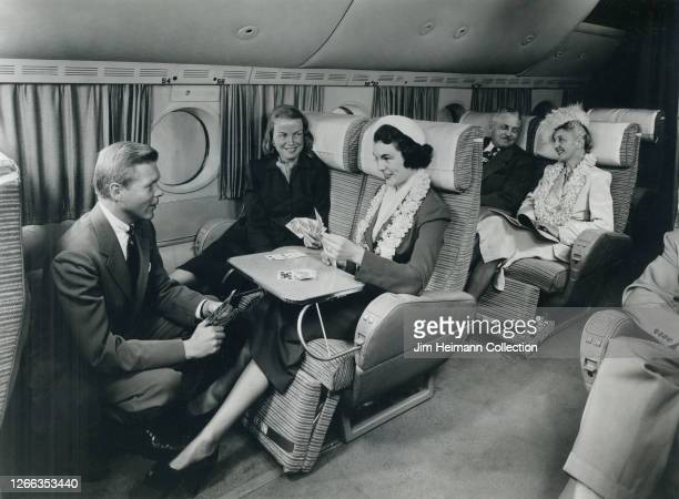 Inflight passengers play cards and make conversation on a spacious airliner circa 1949