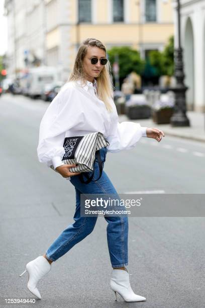 Influencer Alex Seifert wearing a white blouse by SoSue denim jeans by Mango white boots by Marc Cain and a bag by Furla during a street style...