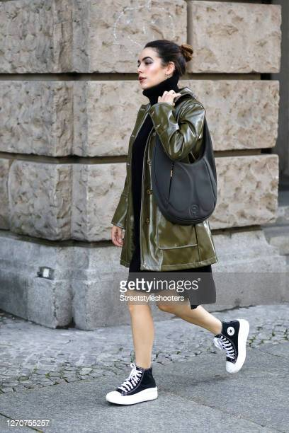 Influencer and model Frankie Miles wearing jewelry by Ariane Ernst, a midi length black turtleneck dress by Tommy Hilfiger, an olive green wetlook...