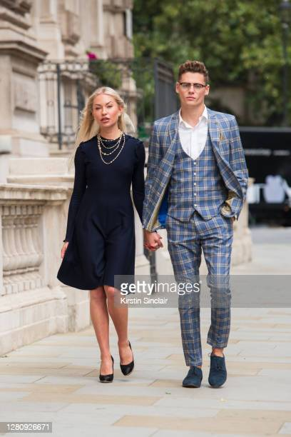 Influencer and model Lexi Fargo wears a Chanel dress, necklace, earrings and shoes with Model and Influencer Angus Findlay wearing a Marc Darcy suit,...