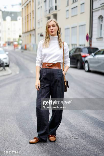 Influencer and model Marlies Pia Pfeifhofer wearing a white turtleneck pullover by Allude, black wide leg pants with white pin stripes by Tory Burch,...