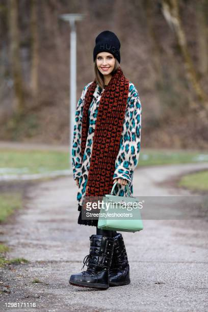 Influencer and TV host Cathy Hummels wearing a mint green bag by Hermes, black faux leather pants by Sassy Classy, a cream colored faux fur coat with...