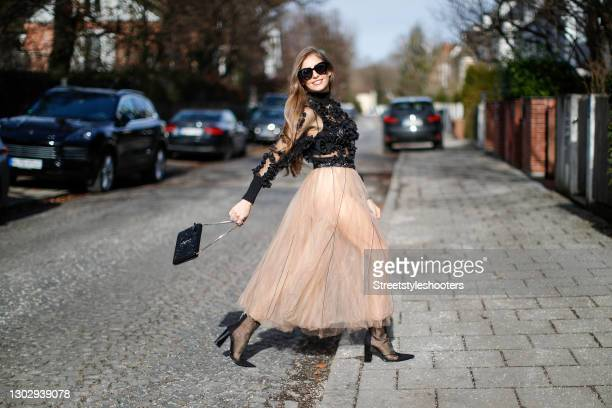 Influencer and TV host Cathy Hummels wearing black mesh high heel boots by Zara, a long beige tulle skirt by Dorothee Schumacher, a black belt with...