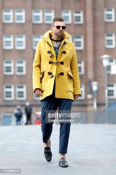 Influencer Andre Borchers wearing a yellow wool and cashmere duffle coat by Gucci, a multicolored shirt by Zara, dark blue pants by H&M, black...