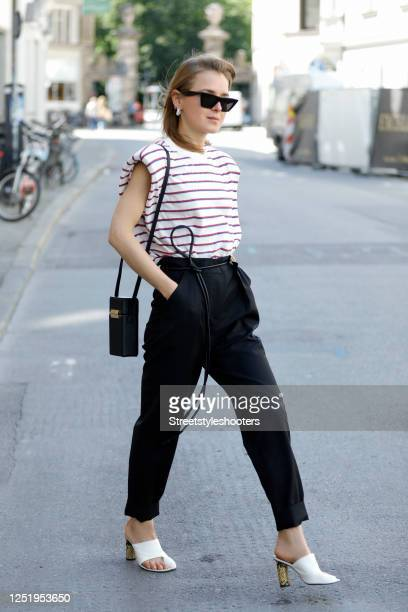 Influencer Anna Borisovna, wearing a black suit by Envelope 1976, a white shirt with blue and red stripes by Mango, white sandals with python heels...