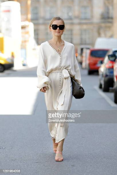 Influencer Anna Borisovna, wearing a long creme colored dress by Envelope 1976, pink sandals by Billi Bi, a dark brown leather bag by Massimo Dutti...
