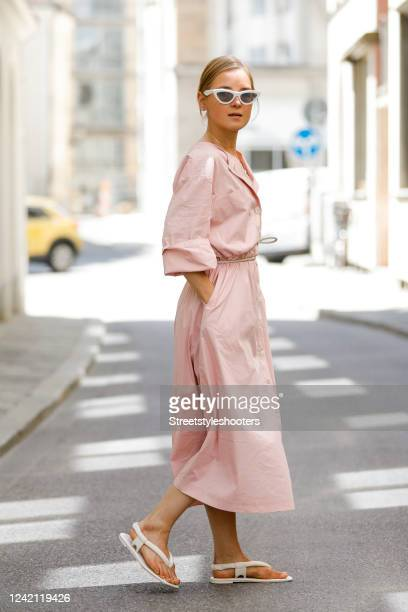 """Influencer Anna Borisovna, wearing a rosa maxi dress by Mango, a leather belt by """"nCos, gold alphabet necklace by Celine and cat-eye white sunglasses..."""