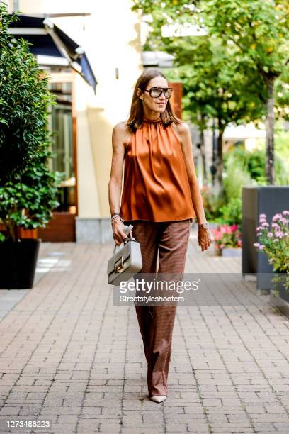 Influencer Annette Weber wearing a bronze colored shirt by Aspesi, brown patterned pants by Aspesi, a beige bag by Bally and sunglasses by Sun...