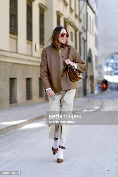 Influencer Annette Weber wearing a cream colored knitted pullover by Weekend Max Mara, beige wide leg pants by Max Mara, a brown leather jacket by...