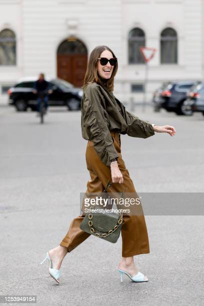 Influencer Annette Weber wearing a green blouse by Baum und Pferdgarten, brown leather pants by Gestuz, mules by Bottega Veneta and a green bag by...
