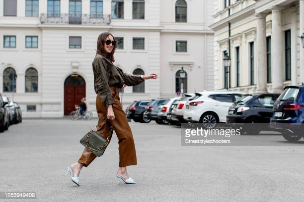 Influencer Annette Weber wearing a green blouse by Baum und Pferdgarten, brown leather pants by Gestuz, light blue mules by Bottega Veneta and a...