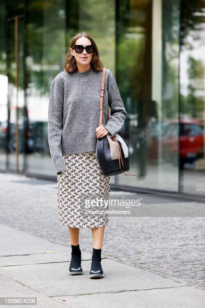 Influencer Annette Weber, wearing a grey pullover by Gembalies, a beige checked skirt by Tory Burch, a black, beige and brown bag with mixed material...