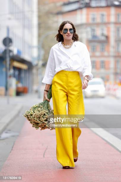 Influencer Annette Weber wearing a white blouse by Seidensticker, yellow wide leg pants by Max Mara, brown sandals by Saint Laurent and sunglasses by...