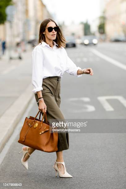 Influencer Annette Weber, wearing a white button down shirt by Seidensticker, khaki colored culottes by Mango and a brown shopper bag by Hermes...