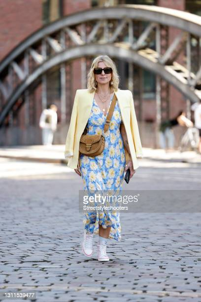 Influencer Carina Grendel wearing a pastel yellow blazer by Zara, a long light blue maxi dress with pastel yellow floral print by Rixo, white sneaker...