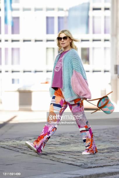 Influencer Carina Grendel wearing sunglasses by Saint Laurent, a purple shirt by Liv Bergen, multicolor floral print pants by Stegmann Hamburg, white...