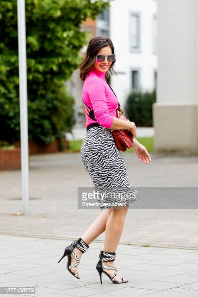 Influencer Dany Michalski wearing a pink turtle neck shirt by Hilfiger a zebra patterned skirt by Fenn Wright Manson Studio zebra heels by Balmain a...