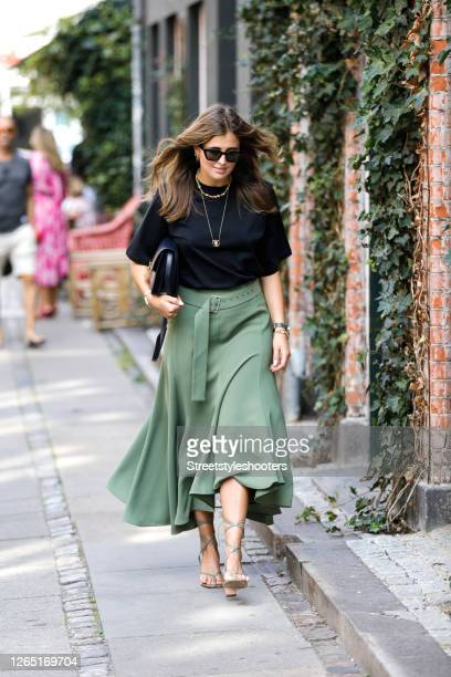 Influencer Darja Barannik, wearing a black shirt, a long green skirt, a black bag and green sandas by Bottega Veneta seen at Copenhagen Fashion Week...