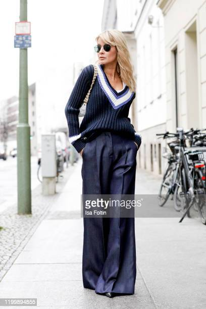 Influencer GItta Banko is wearing a blue vintage sweater by Chanel blue pants by Glamoda a white belt bag by Chanel and balck boots by Yeezy during...
