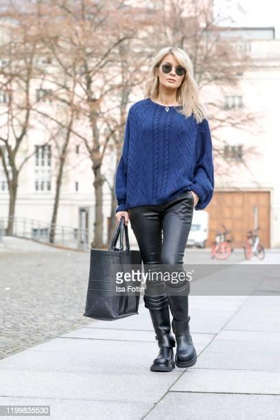 Influencer Gitta Banko is wearing a dark blue oversized cashmere sweater by Boscana, black leather pants by Hironae, biker boots by Bottega Veneta...