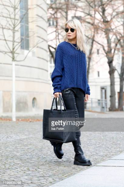 Influencer Gitta Banko is wearing a dark blue oversized cashmere sweater by Boscana black leather pants by Hironae biker boots by Bottega Veneta and...