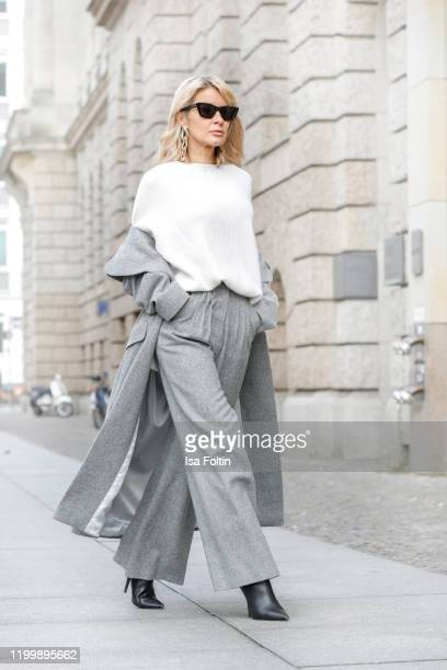Influencer Gitta Banko is wearing a grey oversized coat and grey wool pants by Boscana x Gitta Banko a white cashmere sweater by Nobili Cashmere and...