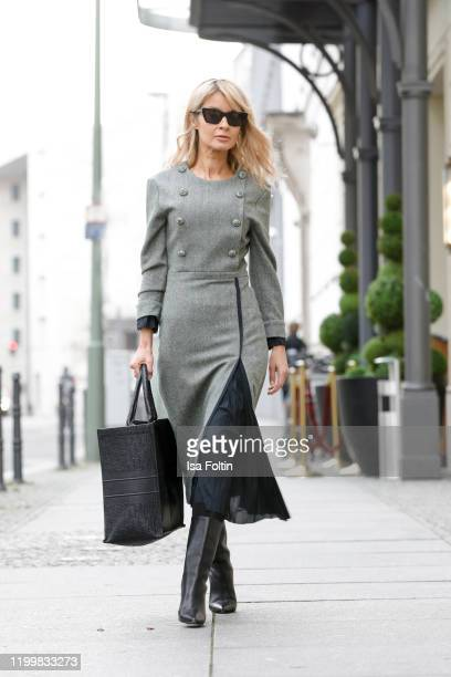 Influencer GItta Banko is wearing a grey wool dress with pleated details by Boscana x Gitta Banko, black leather boots by Yeezy a black leather bag...