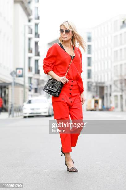 Influencer Gitta Banko is wearing a red oversized sweater by Boscana red pants from TRE by Natalie Ratabesi black mesh pumps by Bottega Veneta and a...