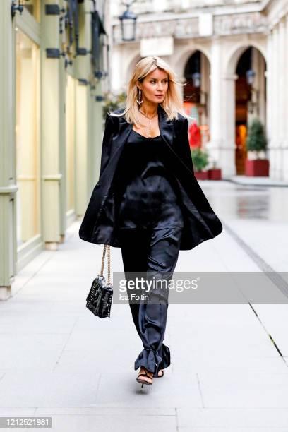 Influencer Gitta Banko, waering a black silk suit and a black silk top by Boscana, a transparent Fendi bag, black strep sandals by Aquazzura and a...