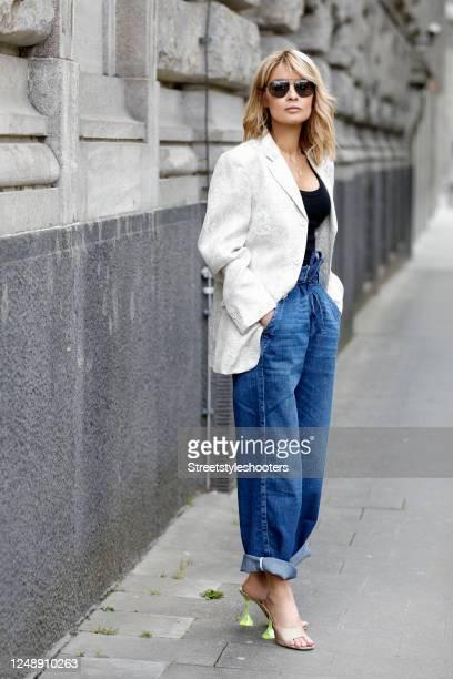 Influencer Gitta Banko, wearing a beige blazer by Comme Des Garcons, gold glitter lupita glass sandals with neon yellow heels by Amina Muaddi, dark...