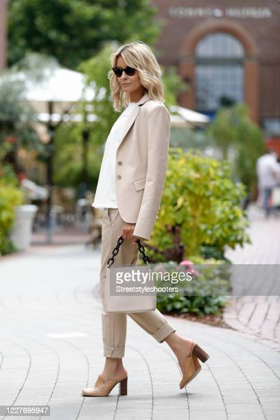 Influencer Gitta Banko wearing a beige blazer by Patricia Pepe, beige pants by 7 for all mankind, a cream colored denim jeans shirt without sleeves...
