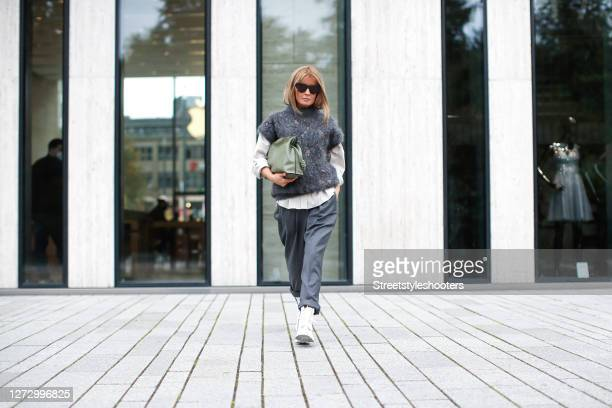 Influencer Gitta Banko wearing a beige blouse by Brunello Cucinelli, grey pants by Brunello Cucinelli, a grey slip-over with sequin details by...