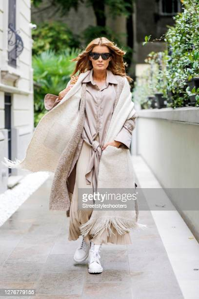 Influencer Gitta Banko wearing a beige colored knitted dress by Zara white chunky boots by Common Projects a beige oversize blouse by Gitta Banko a...