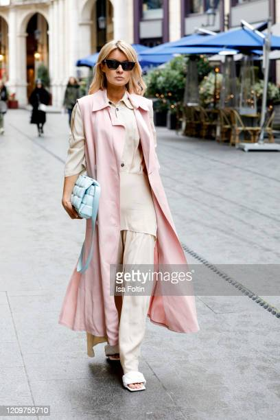 Influencer Gitta Banko, wearing a beige colored pleated dress and a rose colored long vest by Liviana Conti, a topas colored padded cassette bag by...