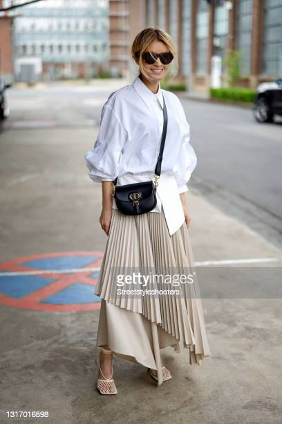 Influencer Gitta Banko, wearing a beige pleated maxi skirt with a white leather belt by Nobi Talai, a white blouse by Nobi Talai, a black bag by...