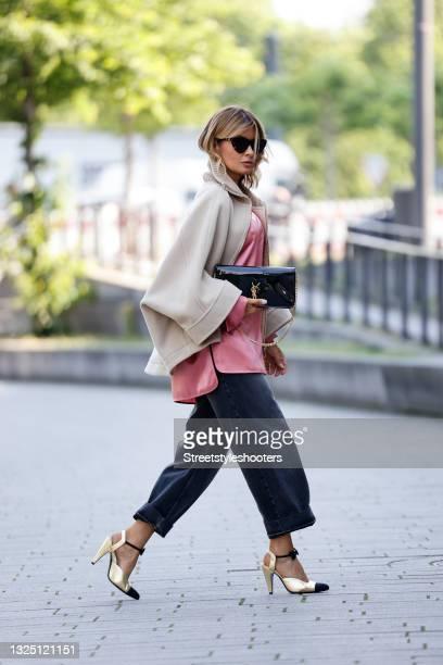 Influencer Gitta Banko wearing a beige short oversized cape-coat by Chloe, a pink silk top by max Mara, grey-blue denim jeans pants by Balenciaga, a...