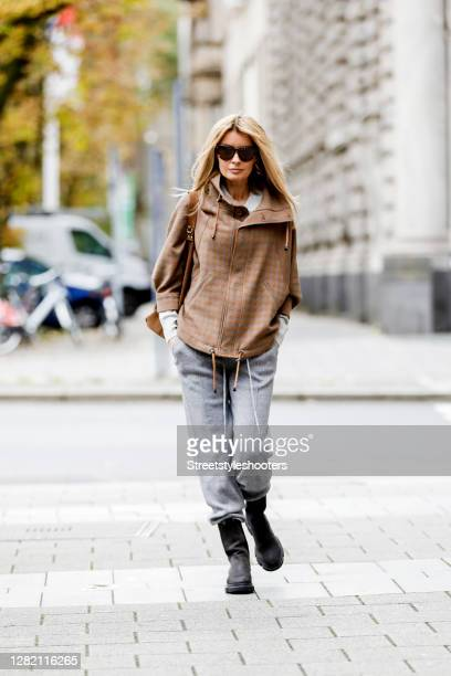 Influencer Gitta Banko, wearing a beige-grey short checked jacket, a light grey knitted poloshirt, light grey knitted pants and a brown suede bag by...