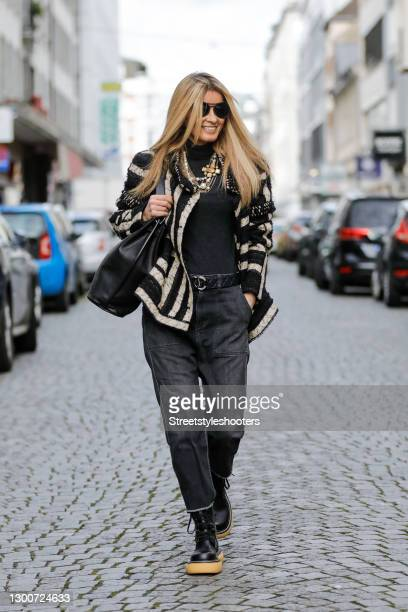 Influencer Gitta Banko wearing a black and cream colored striped jacket by Chanel, a gold layered chain and pearl necklace by Chanel, black...