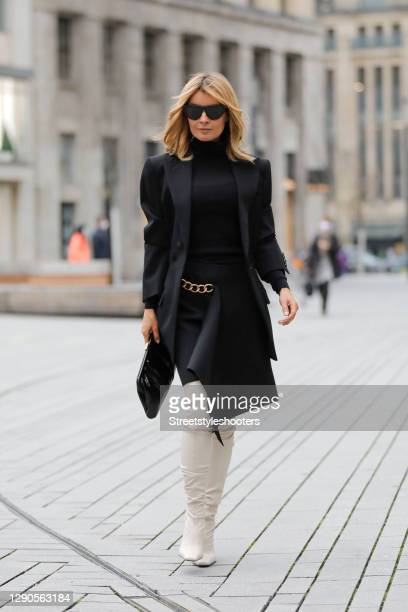Influencer Gitta Banko wearing a black asymmetric skirt with a gold chain at the hip by Givenchy, a black blazer by Givenchy, cream colored overknee...