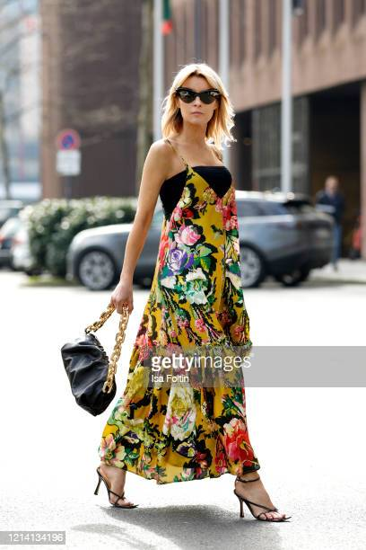 Influencer Gitta Banko wearing a black bandeautop by Zara a floral printed dress by Dries van Noten a black chain pouch bag and black sandals by...