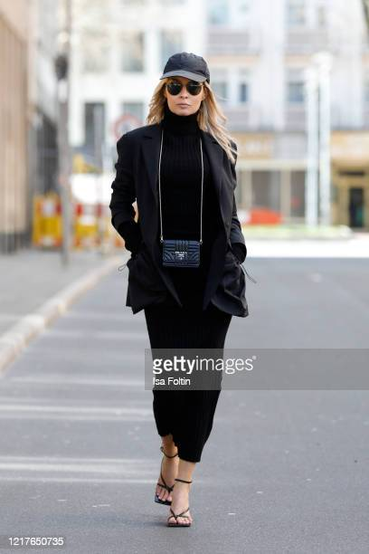 Influencer Gitta Banko, wearing a black blazer by Annette Goertz, a black backless knitted dress by Jacob Lee, black sandals by Bottega Veneta, a...
