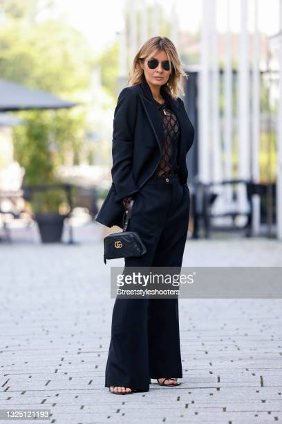 Influencer Gitta Banko wearing a black blazer by Gucci, black marlene pants by Gucci, a black transparent mesh top with black all over logo design by...