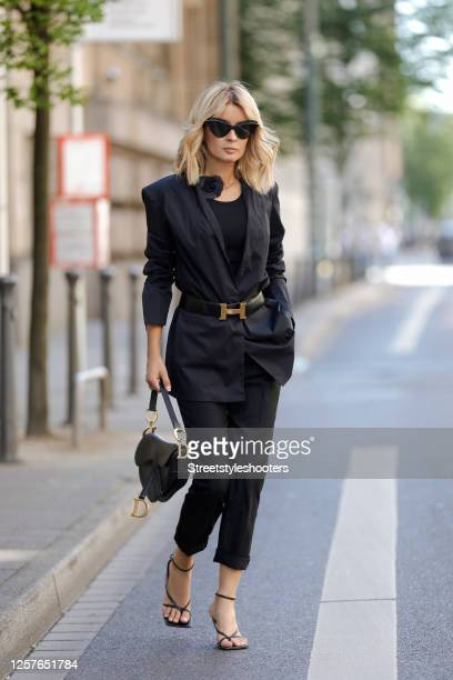 Influencer Gitta Banko wearing a black blazer by Liviana Conti, black pants by H&M, a black shirt by Zara, a black necklace with a Camelie by Chanel,...